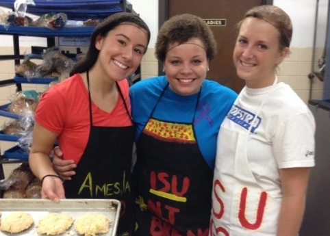 Brittney Carpio, Vanessa McNeal and Shaney Esparza work to combat hunger by making chicken burgers with onion and celery at Campus Kitchens in St. Louis. Contributed photo.