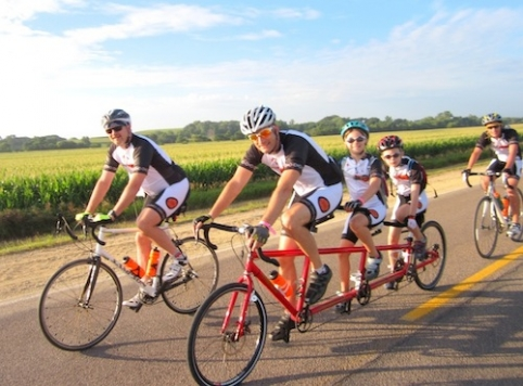 Iowa State alum Jay Alberts, riding a tandem bicycle with his children during RAGBRAI, changes the lives of many people with Parkinson's disease via his Pedaling for Parkinson's initiative. Contributed photo.